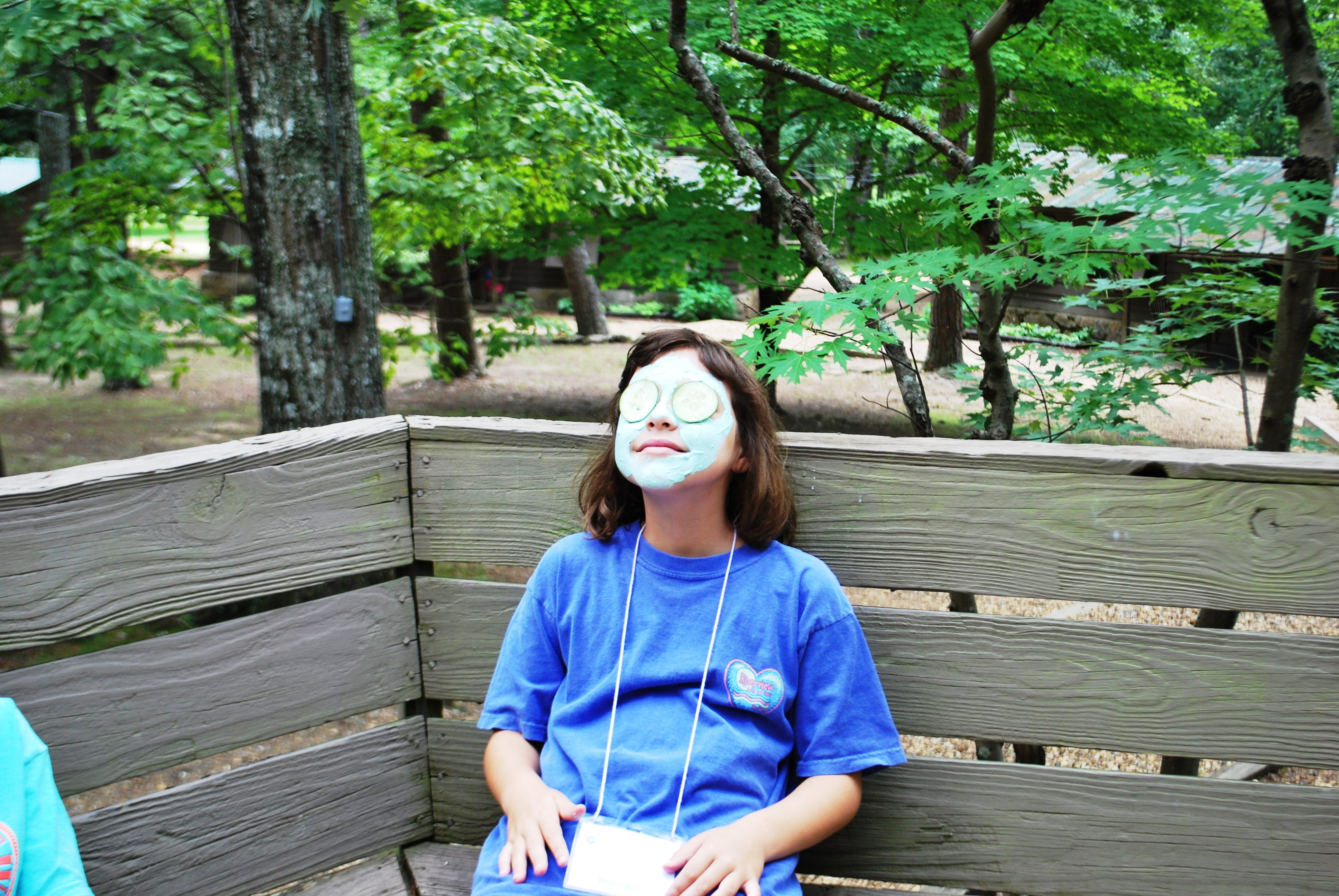 Pre-teen with facial mask and cucumbers over eyes