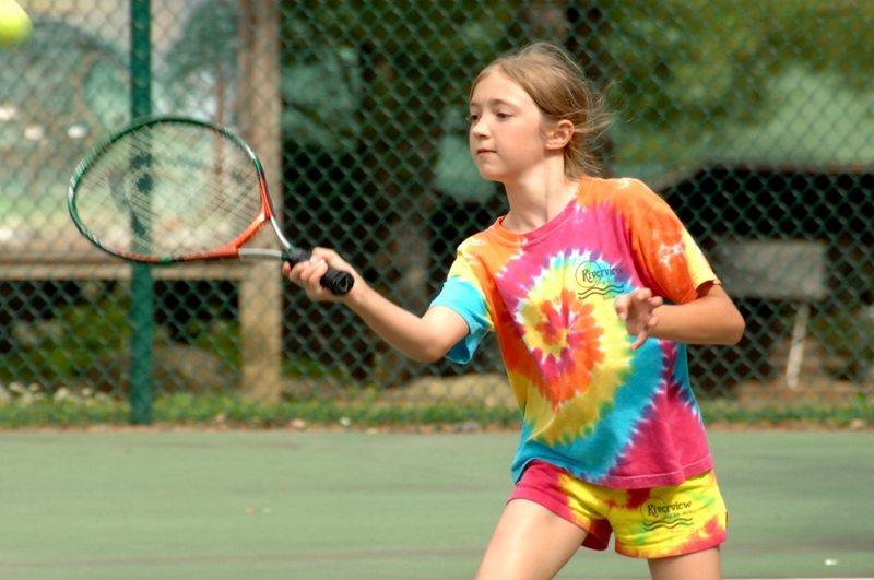 Happy girl hitting tennis ball